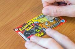 供以人员抓一个波兰乐透纸牌抽奖断续装置在木桌 免版税库存照片
