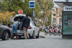 供以人员投入他的手提箱在出租汽车树干 免版税库存图片