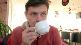 供以人员抚摸茶在咖啡馆的手 人在餐馆用热的饮料和蛋糕 股票录像