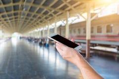 供以人员拿着一个巧妙的电话在火车站的一个时钟下 背景概念查出的目的程序时间白色 免版税库存图片
