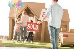 供以人员拿着与搬入新的cardbord房子的年轻家庭的被卖的牌 库存图片