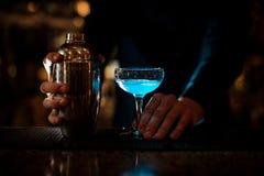 供以人员拿着与蓝色夏天鸡尾酒和瓶的手一块玻璃 免版税库存图片