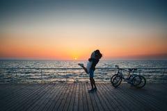 供以人员拿着他的女朋友,亲吻在海滩的年轻恋人夫妇在日出天空在木甲板夏时 免版税库存图片