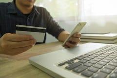 供以人员拿着信用卡和使用智能手机付款shoppin的 免版税图库摄影