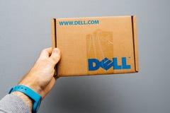 供以人员拿着反对灰色背景与DELL商标的纸板 免版税库存图片