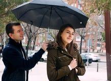 供以人员拿着在可爱的女孩的一把伞 免版税库存图片