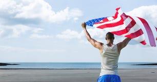 供以人员拿着在海滩的美国旗子 免版税库存照片