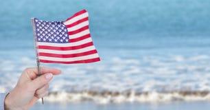 供以人员拿着在海滩的美国旗子 图库摄影