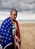 供以人员拿着在海滩的美国旗子 库存图片