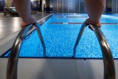 供以人员拿着在游泳池的` s手扶手栏杆 免版税库存照片