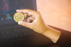 供以人员拿着在计算机膝上型计算机的手金黄bitcoin在与财政图表的背景中 免版税库存图片