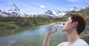 供以人员拿着干净的新鲜的矿物自然水瓶,与山的饮用水室外下面夏天热在自然背景中 库存照片