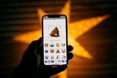 供以人员拿着新的苹果计算机iPhone x智能手机反对与anim的星 免版税图库摄影