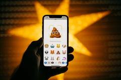 供以人员拿着新的苹果计算机iPhone x智能手机反对与anim的星 库存图片