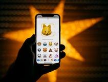 供以人员拿着新的苹果计算机iPhone x智能手机反对与anim的星 免版税库存照片