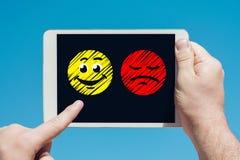 供以人员拿着显示愉快和哀伤的emojis的片剂设备 库存照片