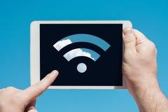 供以人员拿着显示wifi标志和接触s的片剂设备 免版税库存照片