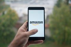 供以人员拿着有亚马逊的智能手机有在屏幕上的手指的 库存照片
