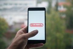 供以人员拿着有任天堂商标的智能手机与在屏幕上的手指 免版税库存图片