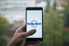 供以人员拿着有偏僻的行星商标的智能手机与在屏幕上的手指 库存图片