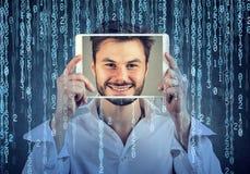 供以人员拿着有在二进制编码背景的一个屏幕上显示的他的面孔的片剂 库存照片