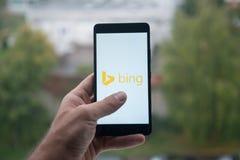 供以人员拿着有微软堆商标的智能手机与在屏幕上的手指 库存图片