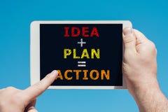 供以人员拿着有文本想法计划行动的一个片剂设备对sc 免版税库存图片