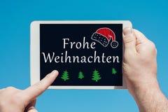 供以人员拿着有文本的一个片剂设备在德国` Frohe Weihnachten `圣诞快乐和接触屏幕 免版税图库摄影