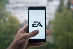 供以人员拿着有电子艺界信使商标的智能手机与在屏幕上的手指 库存图片