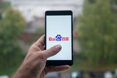 供以人员拿着有百度商标的智能手机与在屏幕上的手指 库存图片