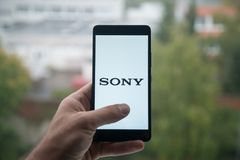 供以人员拿着有索尼商标的智能手机与在屏幕上的手指 免版税库存照片