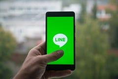 供以人员拿着有线的与手指的信使商标智能手机在屏幕上 图库摄影