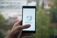 供以人员拿着有维基百科商标的智能手机与在屏幕上的手指 免版税库存图片