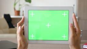 供以人员拿着有绿色屏幕色度大模型的一台大数字式talbet个人计算机在水平的方式下 股票录像