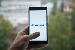 供以人员拿着有联想商标的智能手机与在屏幕上的手指 免版税库存照片