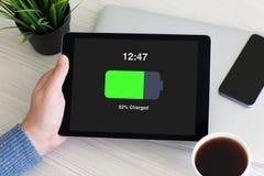 供以人员拿着有被充电的电池的手计算机片剂在屏幕上 免版税库存图片
