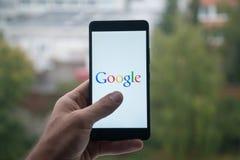 供以人员拿着有谷歌商标的智能手机与在屏幕上的手指 库存图片