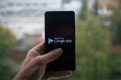 供以人员拿着有谷歌戏剧信使商标的智能手机与在屏幕上的手指 免版税库存照片