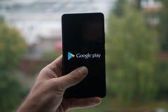 供以人员拿着有谷歌戏剧商标的智能手机与在屏幕上的手指 免版税库存图片