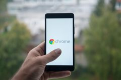 供以人员拿着有谷歌镀铬物的智能手机与在屏幕上的手指 库存照片