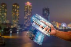 供以人员拿着有透明多屏幕的` s手智能手机在被弄脏的城市夜光 图库摄影