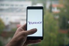 供以人员拿着有雅虎信使商标的智能手机与在屏幕上的手指 免版税库存照片