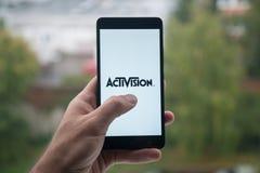 供以人员拿着有Activision商标的智能手机与在屏幕上的手指 库存图片