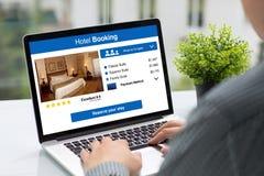 供以人员拿着有app旅馆预定屏幕的计算机在咖啡馆 免版税库存照片