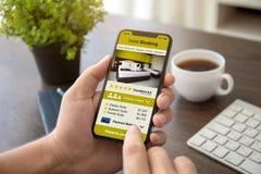 供以人员拿着有app旅馆预定的手电话在屏幕上 免版税库存照片