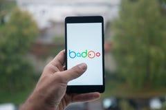 供以人员拿着有Badoo商标的智能手机与在屏幕上的手指 免版税库存图片