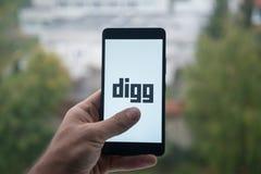 供以人员拿着有Digg的智能手机与在屏幕上的手指 免版税图库摄影