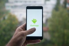 供以人员拿着有Duolingo的智能手机与在屏幕上的手指 免版税库存照片