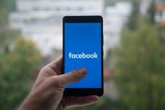供以人员拿着有Facebook商标的智能手机与在屏幕上的手指 免版税库存图片