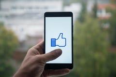 供以人员拿着有Facebook的智能手机象与在屏幕上的手指 免版税库存图片